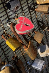 Heart shaped rusty old pad locks on a metal fence