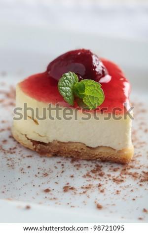 Heart-shaped slice of cheesecake with cherry jam