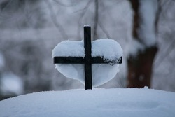 Heart-shaped Snow on a Cross. A lot of snow covered everything on the  ground like the cemetery's gate and tombs. Here's a cross on the gate where a a heart-shaped snow covered it.