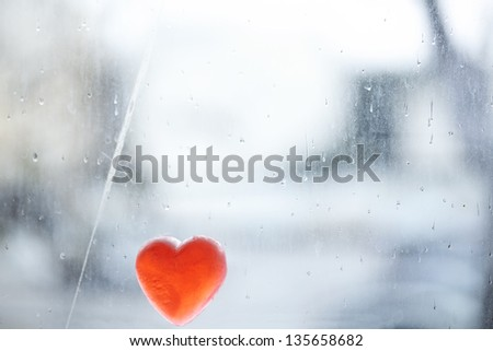 Heart shaped soap leaning on a window covered with rain drops on a winter day.