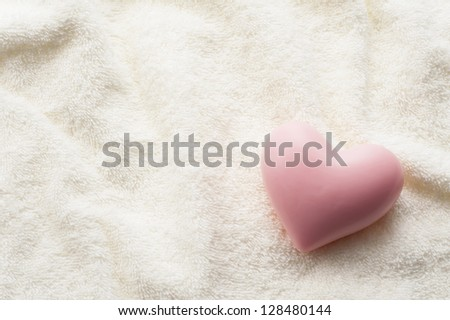 Heart-shaped soap on towel fabric background