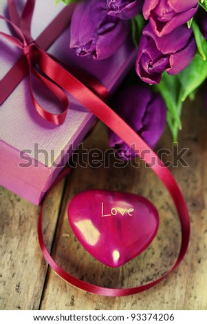 heart-shaped stone, gift box and fresh tulips on wooden board