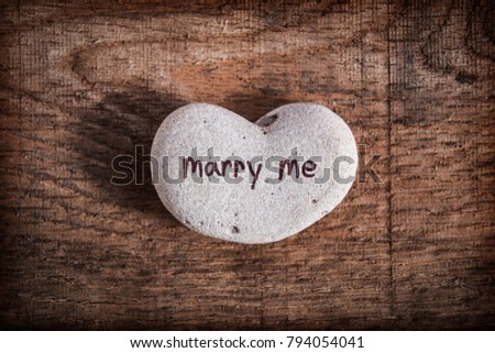 "Heart shaped stone with the words ""Marry me"" written on it with  #794054041"