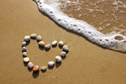 heart-shaped stones on a beach with surf wave