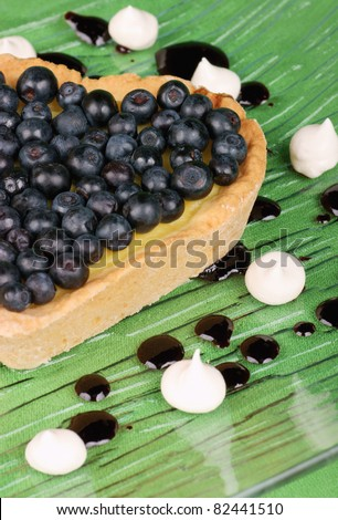 Heart-shaped tart with blueberries served on a glass dish decorated with meringues and topping. Selective focus, soft focus