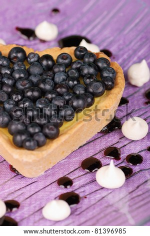 Heart-shaped tart with cream and blueberry served on a glass plate decorated with meringues. Selective focus, shallow DOF