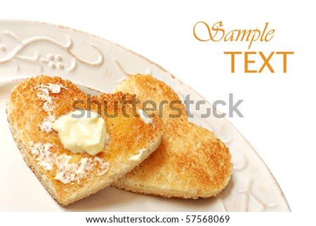 Heart shaped toast with butter on decorative antiqued plate.  White background with copy space.
