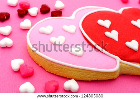 Heart shaped Valentines Day cookies and candies on pink paper background