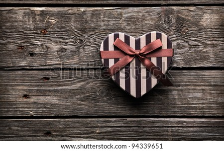 Heart shaped Valentines Day gift box closeup on old wood. Vintage holiday background.