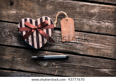Heart shaped Valentines Day gift box with blank gift tag and fountain pen on old wooden background.