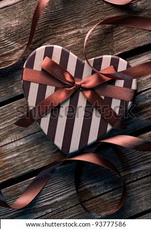 Heart shaped Valentines Day gift box with curved ribbon on old wood. Vintage holiday background.