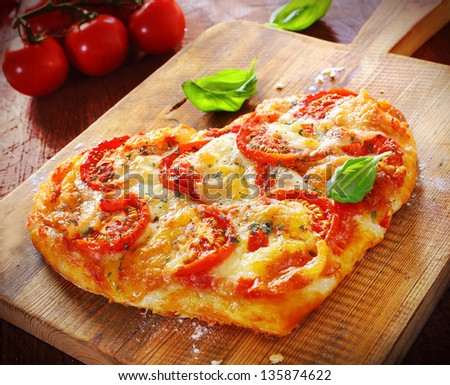 Heart shaped vegetarian pizza topped with cheese and tomato on an old wooden board signifying love of pizza, or romantic love for Valentines day or an anniversary