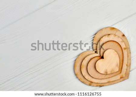 Heart shaped wooden cutouts on light wood. Set of plywood hearts with hole and copy space. Idea for party decoration. #1116126755