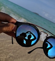Heart silhouette reflection on sunglasses at beach