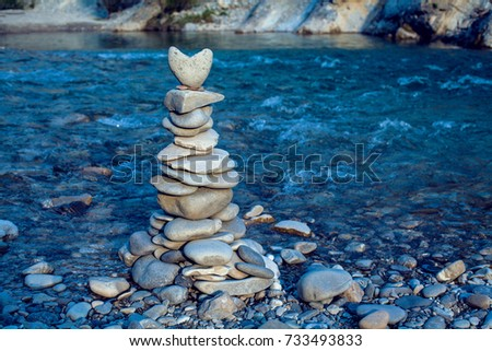 Heart stone pyramid on a floating river