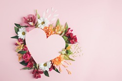 Heart surrounded with fresh colorful flowers on pastel pink background. Creative love layout with copy space. Valentines day, wedding or romantic visual trend. Spring bloom. Flat lay.