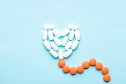 heart symbol formed white pills or tablets isolated on a blue background. above view. outer space. cardiac medicine concept.