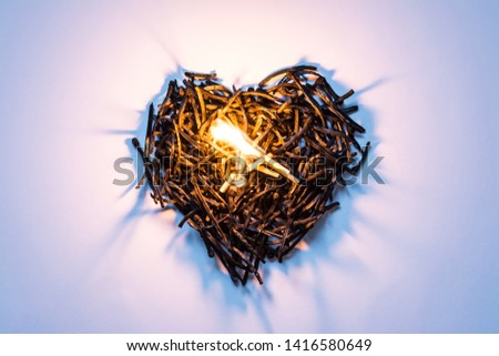 Heart symbol made of burned-down matches close-up with a burning match in the center and beautiful shadows. The concept of the complexity of love relationships, unhappy love.
