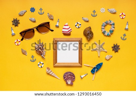 Heart symbol made of decorative items, miniature toys and beach accessories: seashells, sunglasses, bracelet, vessel, life buoys. Empty wooden photoframe, mock up. Summer vacation, sea travel concept #1293016450