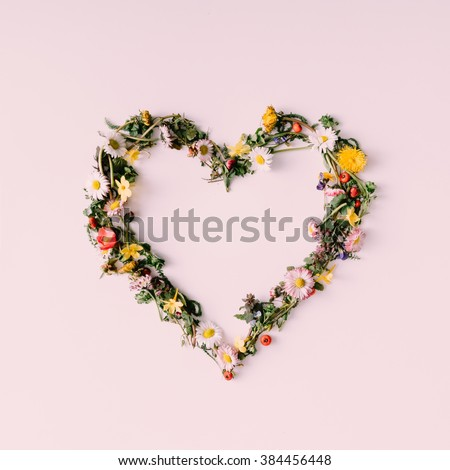 Heart symbol made of flovers and leaves on white background. #384456448