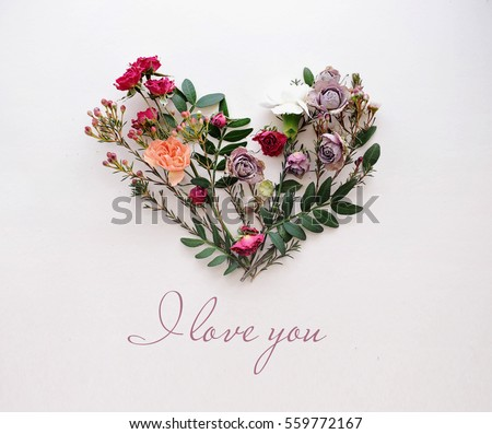 Stock Photo Heart symbol made of flowers and leaves on white background with texting I love you