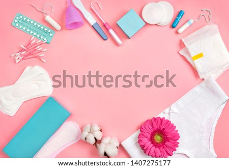 Heart symbol. Sanitary napkins and other hygiene accessories on pink background. Concept of critical days, menstruation #1407275177
