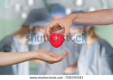 Heart transplant and organ donation concept. Hand is giving red heart. - Shutterstock ID 708590581