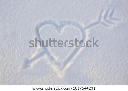 Heart with an arrow drawn on the snow #1017544231