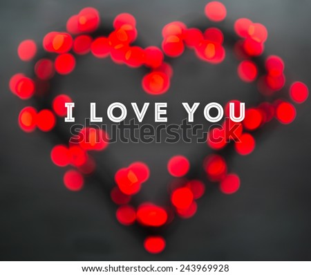 Heart with red blurred lights on wooden dark background. Valentines day card concept