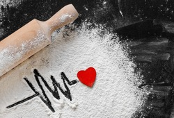 heartbeat shape made with flour and red heart on it. Valentine's Day food concept. Top view, flat lay. rolling pin, flour on blackboard. Love ornament food background