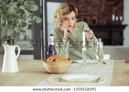 Heartbroken girlfriend. Heartbroken girlfriend sitting at table with alcohol and croissants alone and burning candle #1350558395