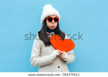 Heartbroken Sad Upset Girl Holding a Heart on Blue Background. Girl feeling blue sad after breakup in time for Valentine's Day   ストックフォト ©