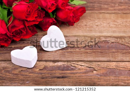 hearts and a bouquet of red roses on wooden board Valentines Day background
