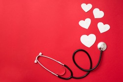 hearts and stethoscope , heart health care concept, red background with copy space