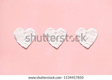 Hearts from cream in pink background. Skin care.