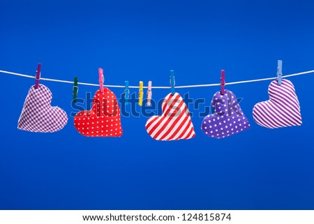 hearts hanging on a clothesline with clothespins, blue background