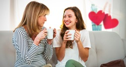Hearts hanging on a line against mother and daughter drinking tea