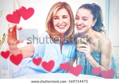 Hearts hanging on a line against mother taking selfie with daughter #569714473