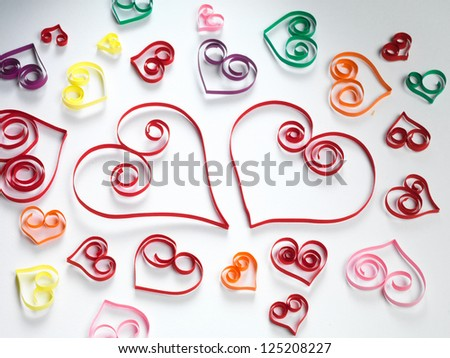 Hearts made of paper stripes on white paper background