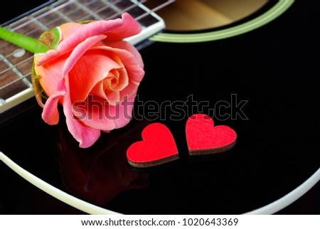 Hearts of lovers, beautiful rose and black acoustic guitar. Valentine's Day. #1020643369
