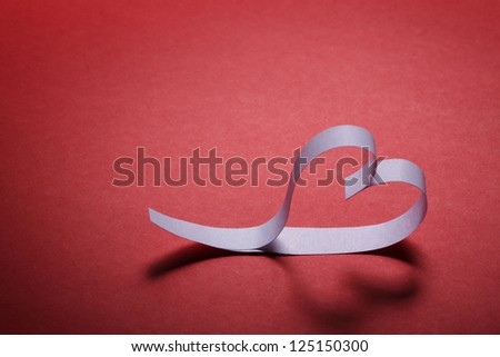 hearts of white paper on a beautiful red background to the Valentine's Day background for Postcards