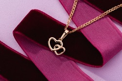 Hearts shape rose gold pendant necklace on pink background. Romantic  jewelry. Advertising still life product concept for Valentines Day