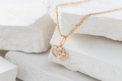 Hearts shape rose gold pendant necklace on white background. Romantic  jewelry. Advertising still life product concept for Valentines Day
