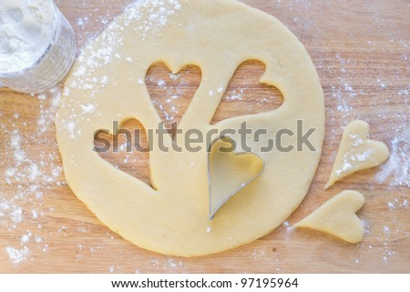 Hearts shaped cookie cutter on raw cookie dough
