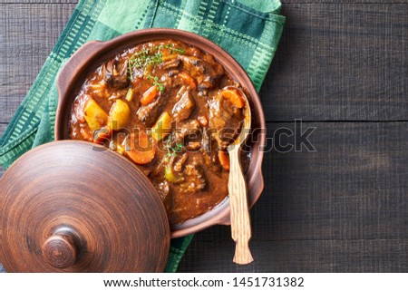 Hearty beer and lamb stew, with potato, carrot, stewed in a dark beer, with thyme stems, served in a clay pot with irish soda bread on a wooden background, top view, copy space Foto stock ©