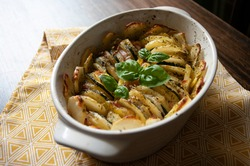 Hearty potato gratin bacon and zucchini,freshly served from the oven on a wooden table.Casserole food,vessel.