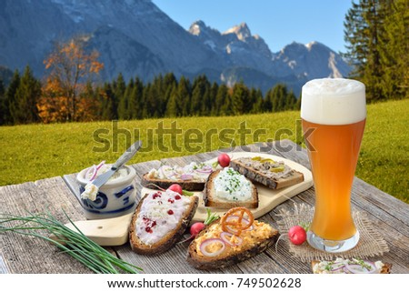 Hearty snack with different kinds of spreads on farmhouse bread served with a fresh yeast wheat beer on an old wooden table in the Bavarian Alps