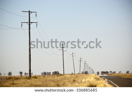 Heat haze rises as powerlines blur into the distance - stock photo
