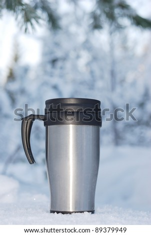 Heat protection-thermos coffee cup on winter day