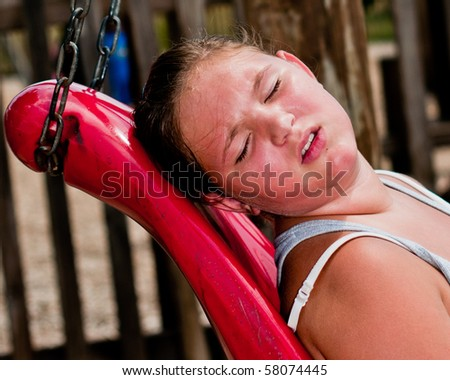 Heat wave concept with girl sweating under the hot sun at playground.